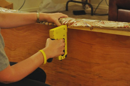 woman using staple gun to attach fabric to wood
