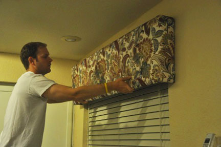 A man hangs a completed DIY box valance above a window in his home