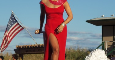 Miss America 2013 Mallory Hagan shows off a vibrant red evening gown at a parade.