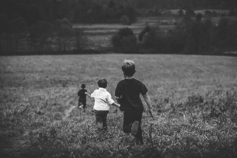 Children running through field, black and white photo