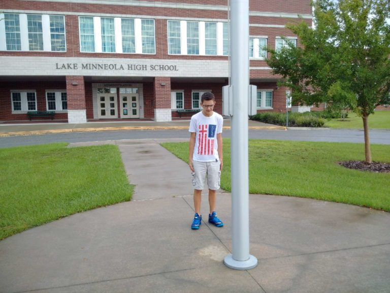 Child at the flagpole in front of school praying