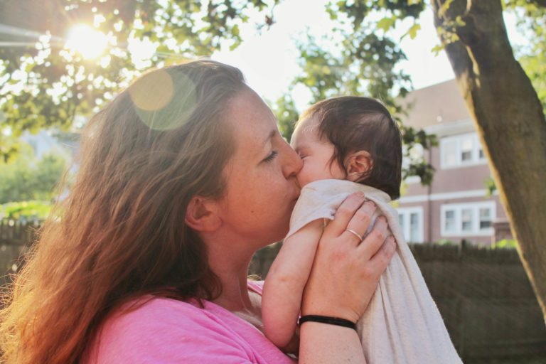 mother kissing baby in sunlight