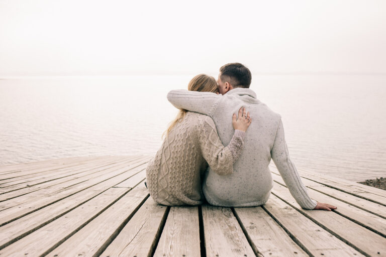 Man and woman sit on the end of a dock with arms around each other