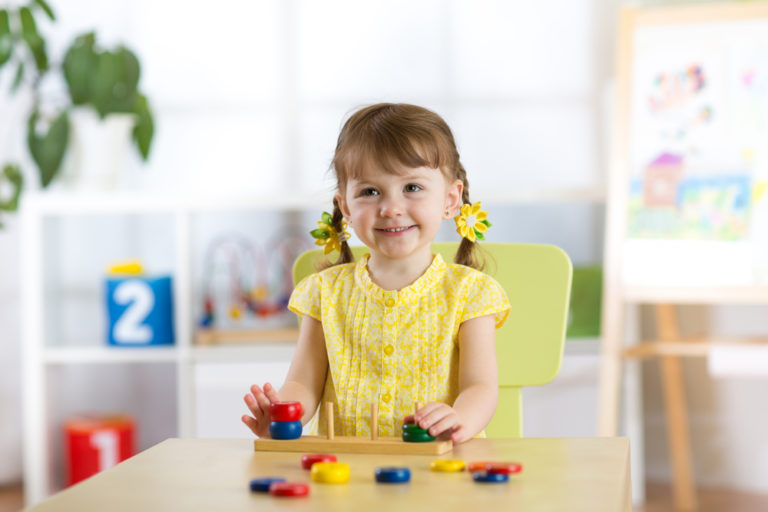 Little girl stacking wooden toys