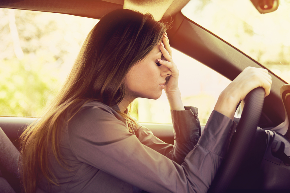 Tired woman with hand on forehead in parked car
