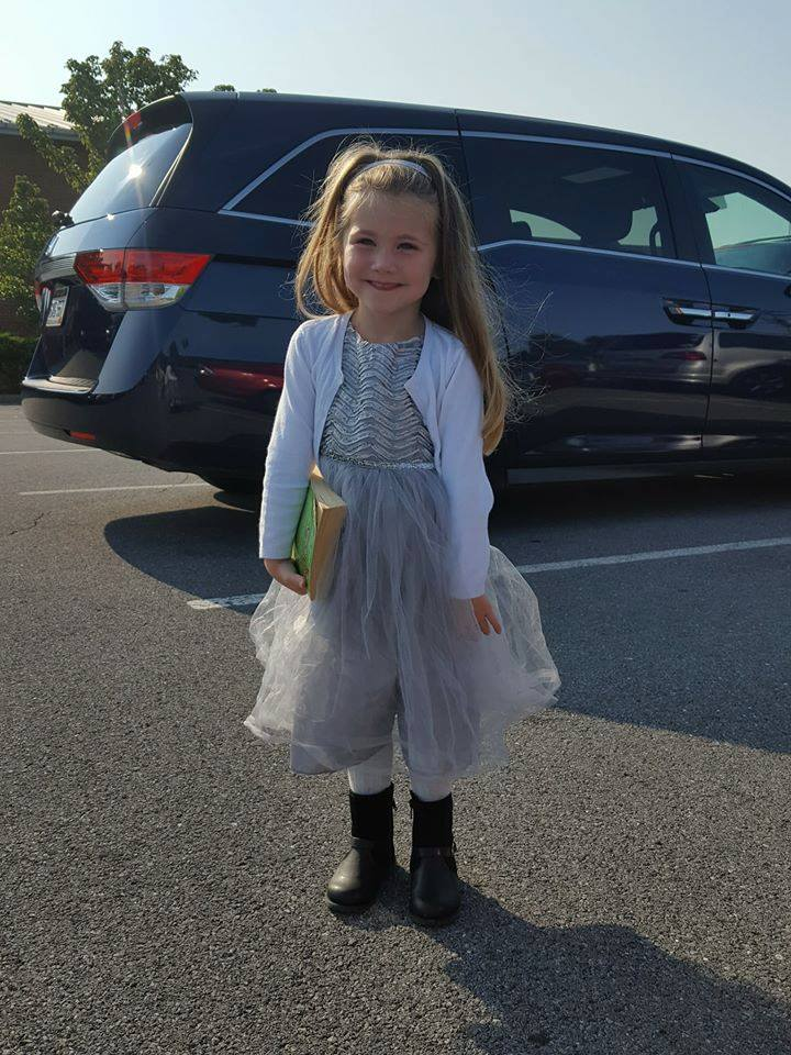 Little girl in dress standing in church parking lot