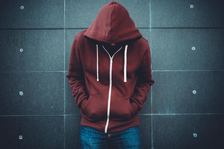 Teen boy in hoodie with head down sad