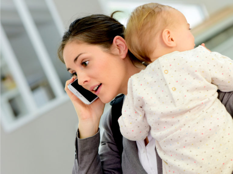 Mom on the phone with baby on her hip
