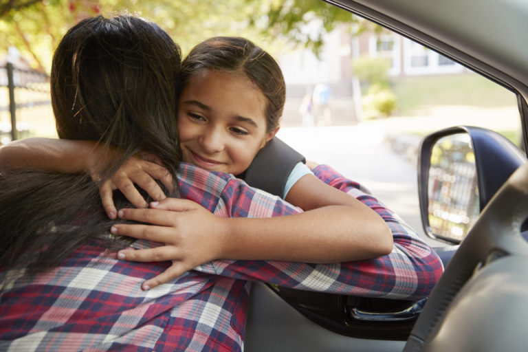 mom hugs child going to school in car www.herviewfromhome.com