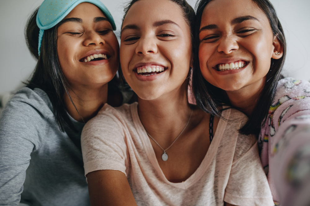 Three young teen girls smiling and laughing
