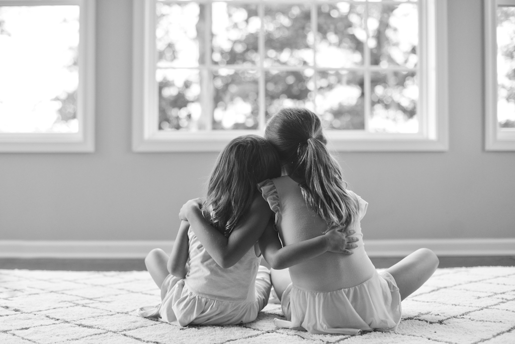 Two young sisters with their arms around each other at home