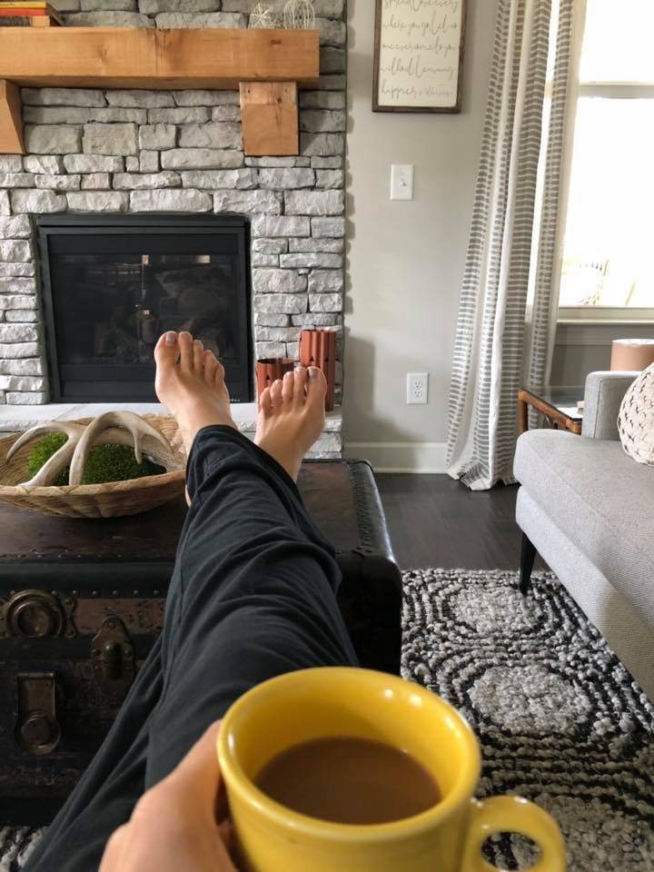 Woman with feet up on coffee table at home