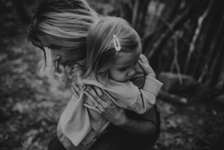 mother hugging her toddler girl black and white