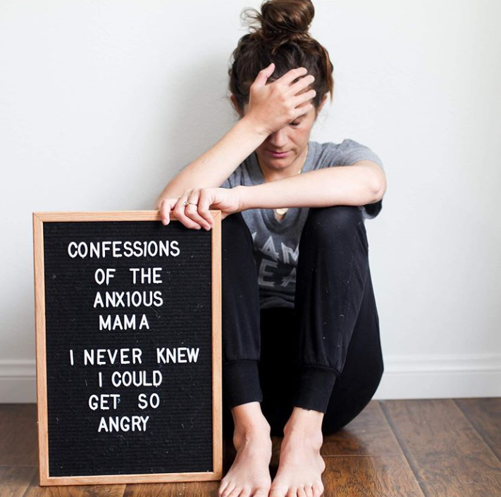 an angry mom sitting by letter board head in hands