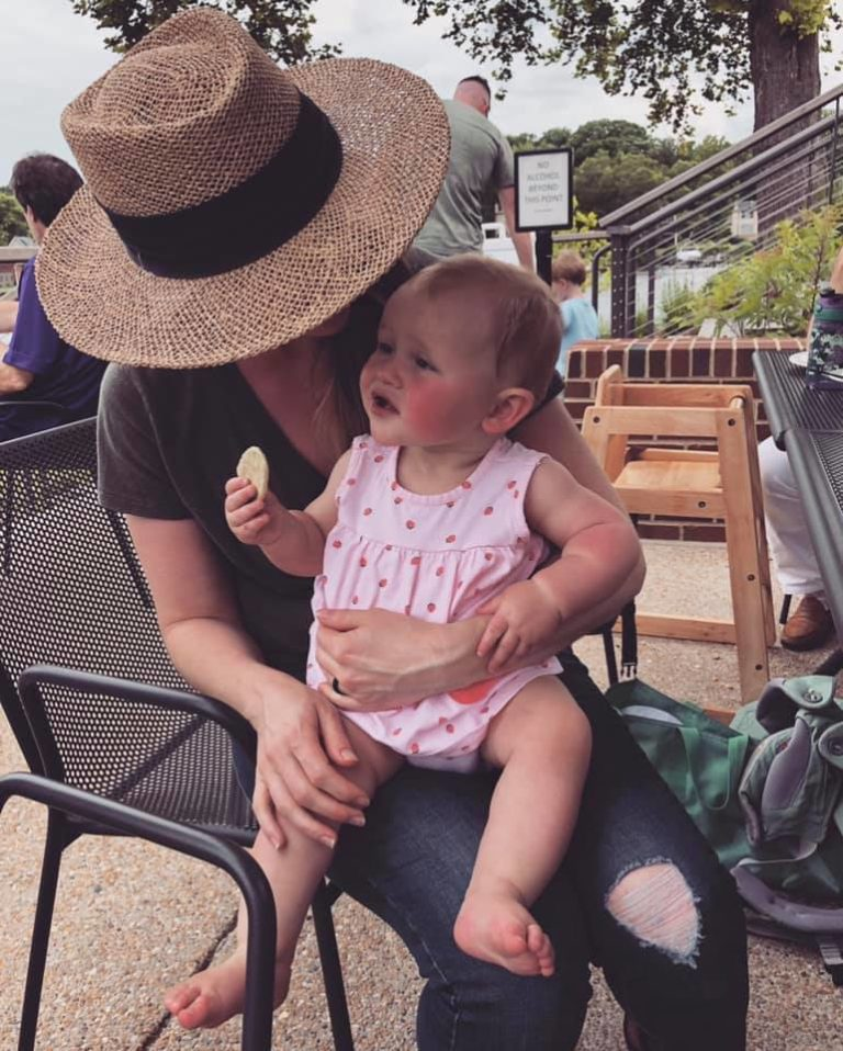 Mother wearing hat sits with toddler daughter on her lap outside