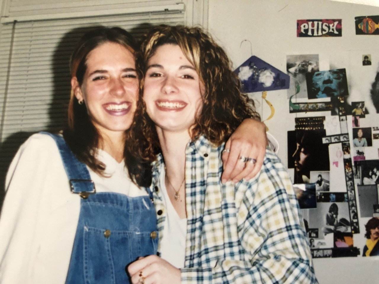 Two college friends hug and smile at the camera