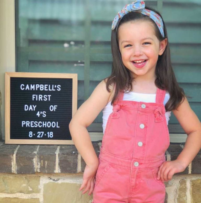 young girl on her first day of school smiles by letterboard