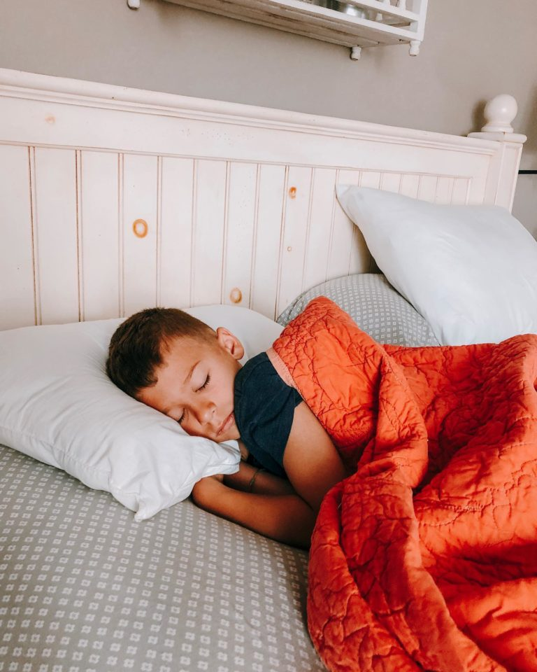 Young boy asleep in his bed at home in early morning