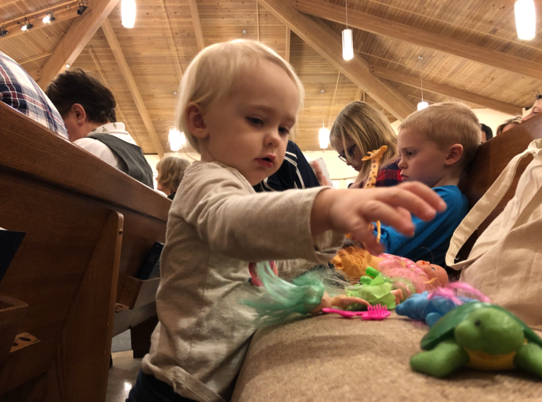 A toddler playing with toys in the church pew Sunday morning