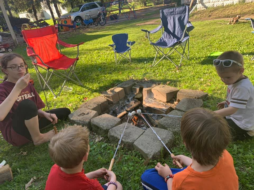kids making S'mores around a backyard campfire in summer