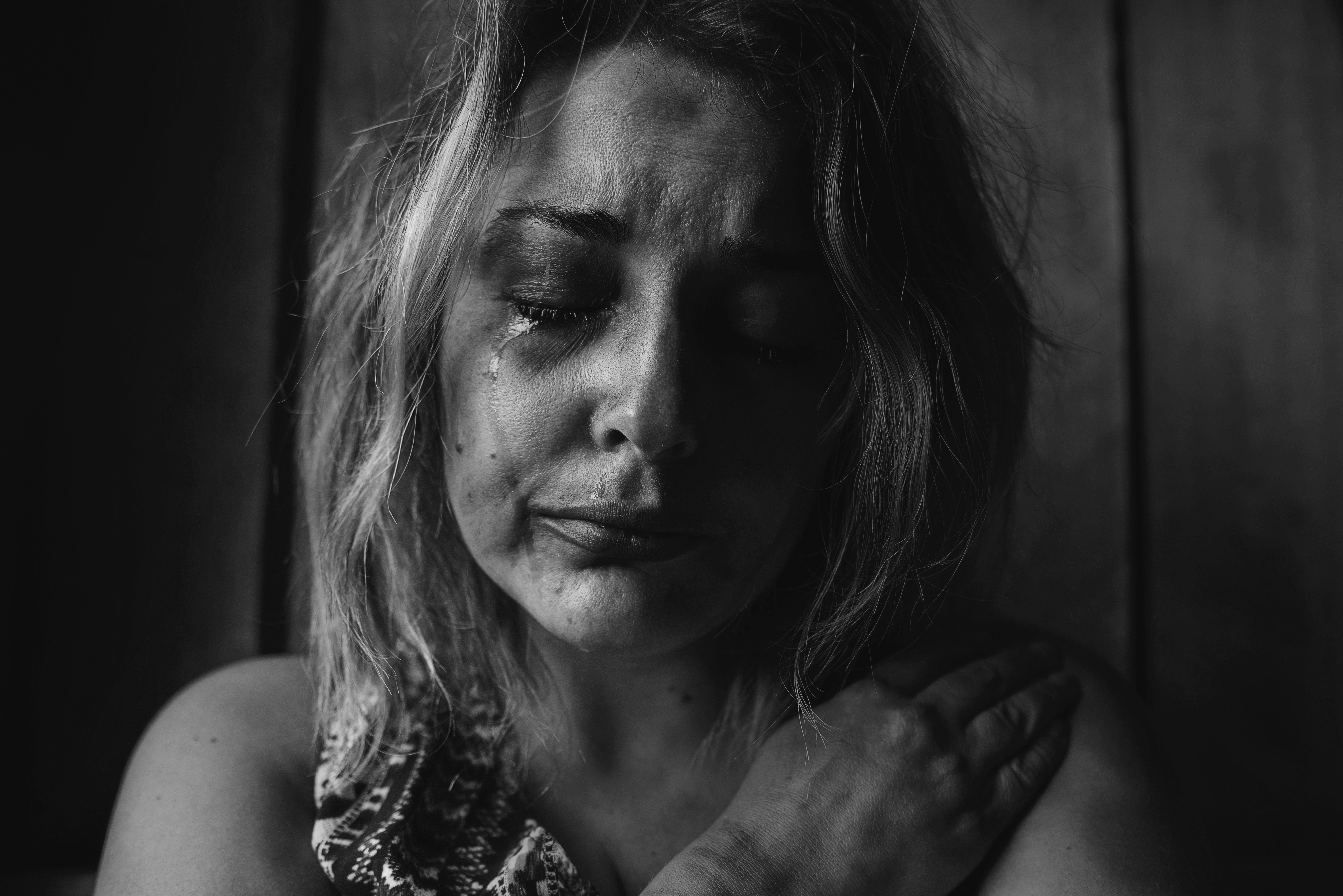 Crying woman in black and white portrait grieving