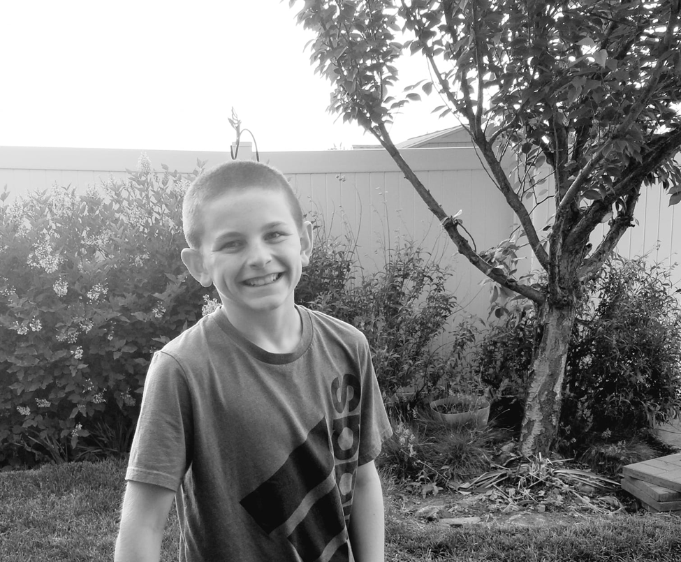 Tween boy holding a ball in the backyard smiling at camera