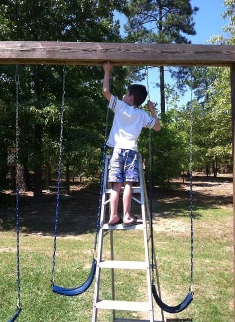little boy on a latter fixing a swing