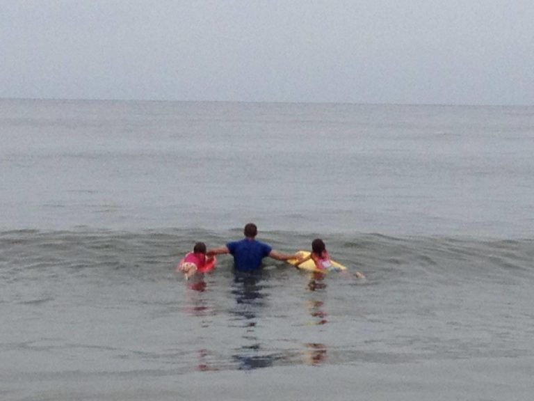 father with two children wading in lake