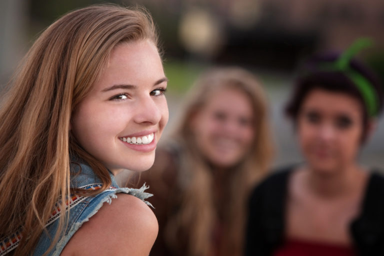 Young teen girl looking over her shoulder with friends in background