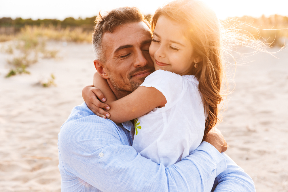Dad and daughter hug on the beach at sunset