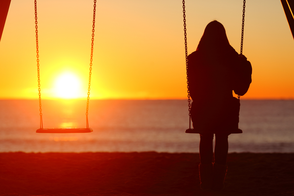 Woman alone on a swing next to empty one at sunset