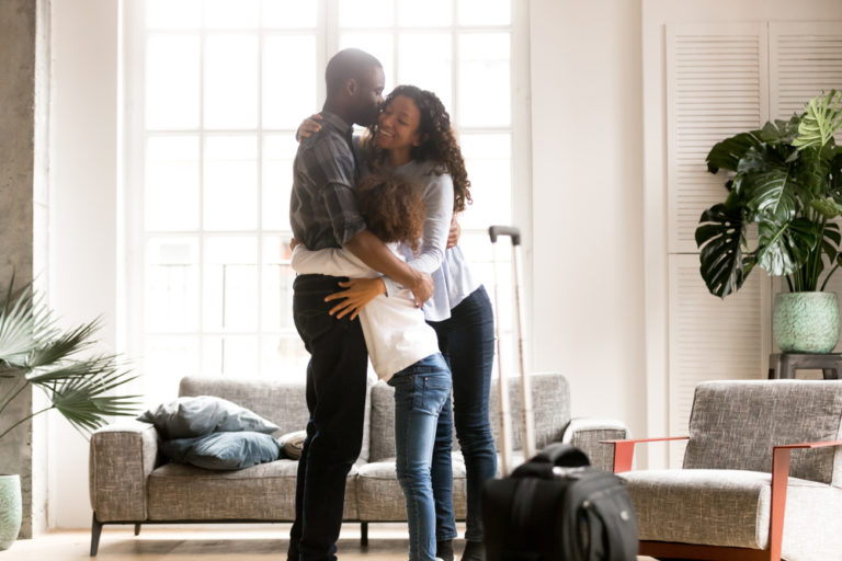 happy african american family hugs at home in living room