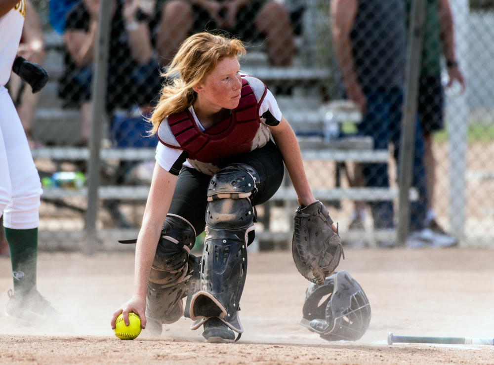 red headed teen girl plays catcher on softball team