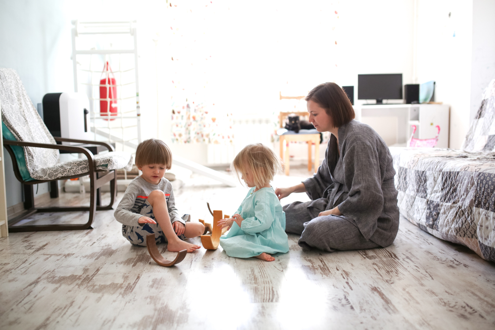 Mother sits on the floor while her two children play at home