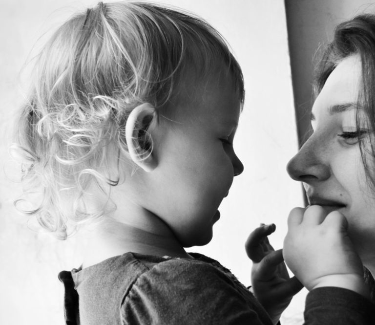 mother smiles at her toddler who is touching her face