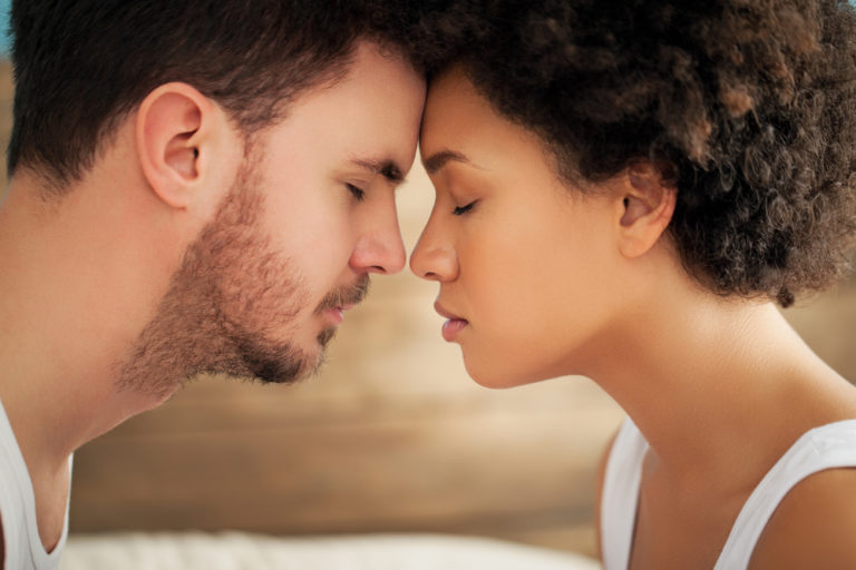 couple with eyes closed touch foreheads