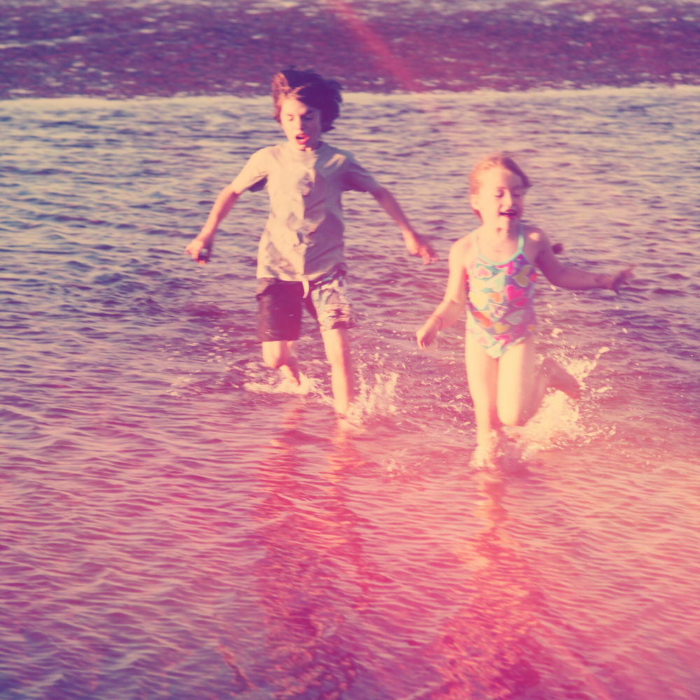 two young children play in a lake in swimsuits