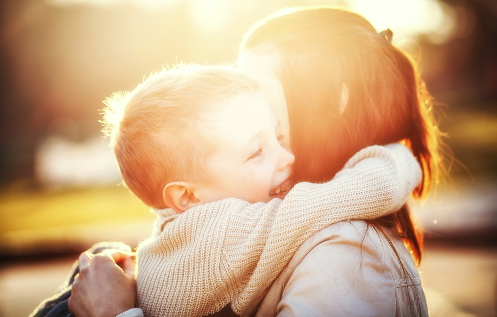 little boy hugs his mother in the sunlight