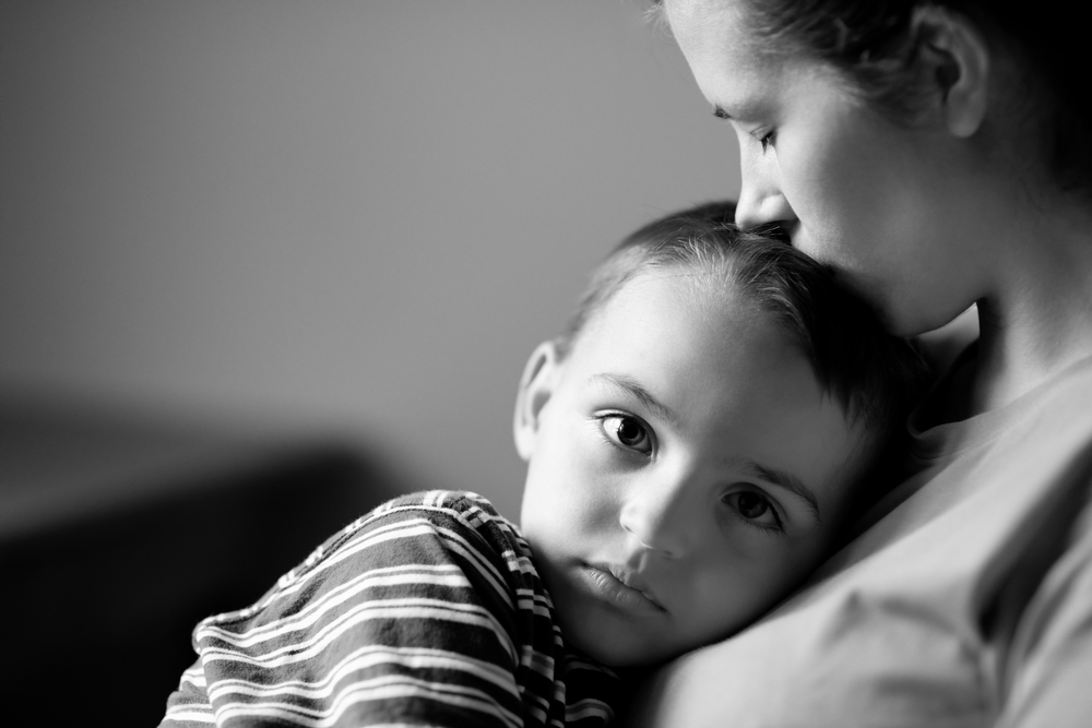 Black and white photo of mother kissing young son