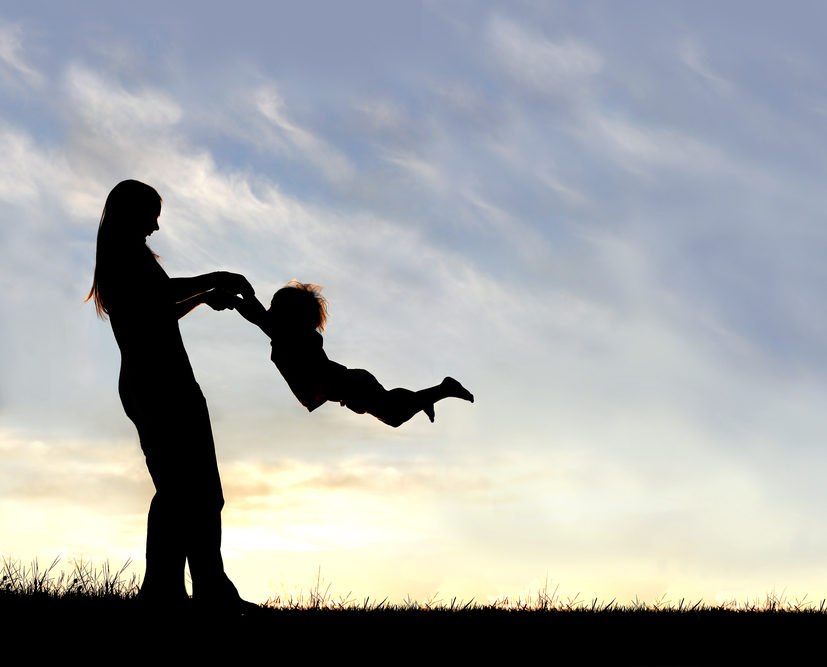 mother and son silhouette dancing together