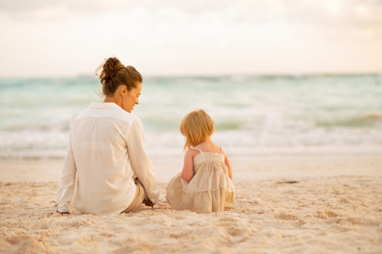 Mother and daughter sitting on beach quietly