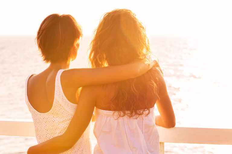 two friends with arms around each other at sunrise