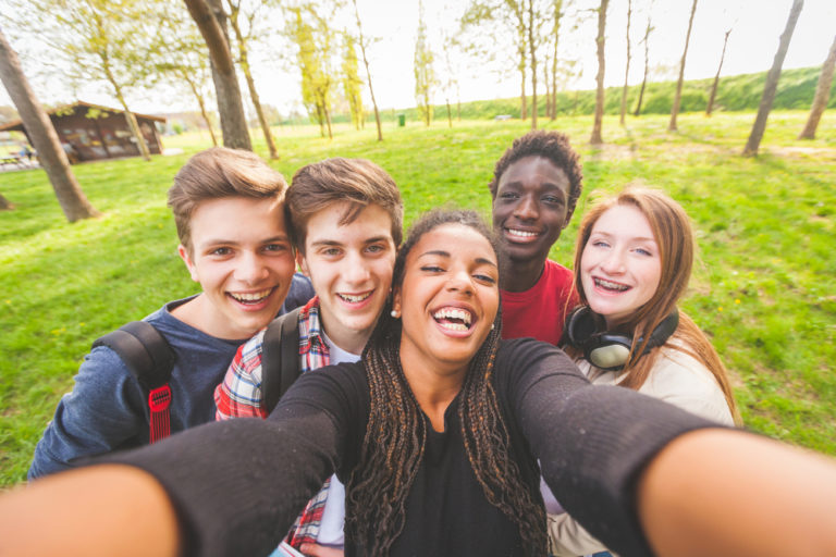 group of teenagers taking a selfie outside