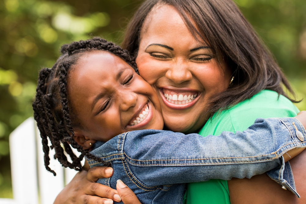 Mother hugging young daughter and smiling