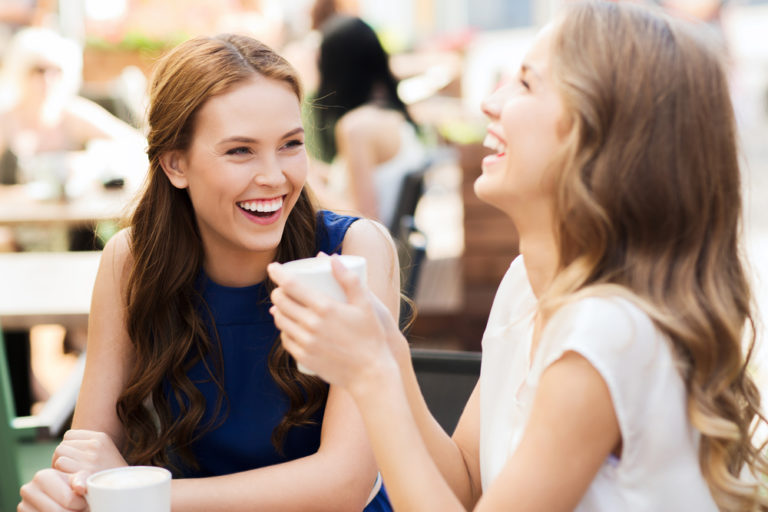 two women friends having coffee outside at a cafe