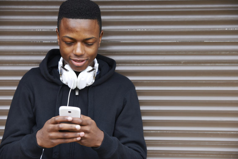 teenage boy with headphones looks at smartphone
