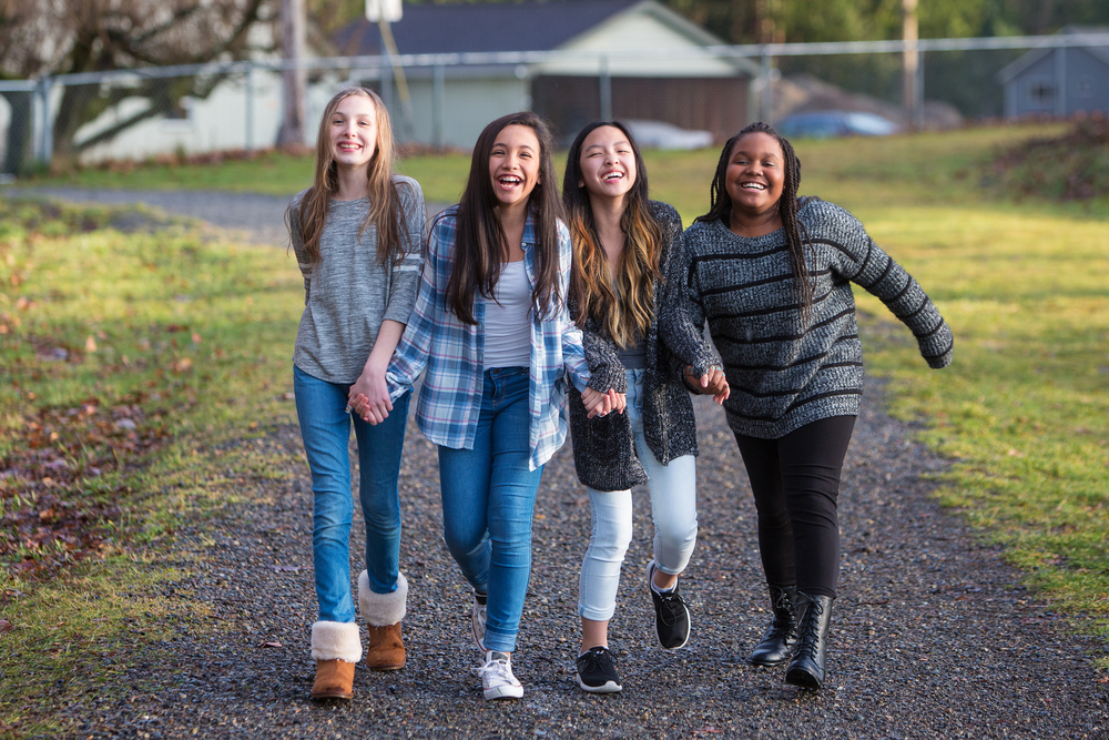 tween girls walk down a path together laughing and holding hands