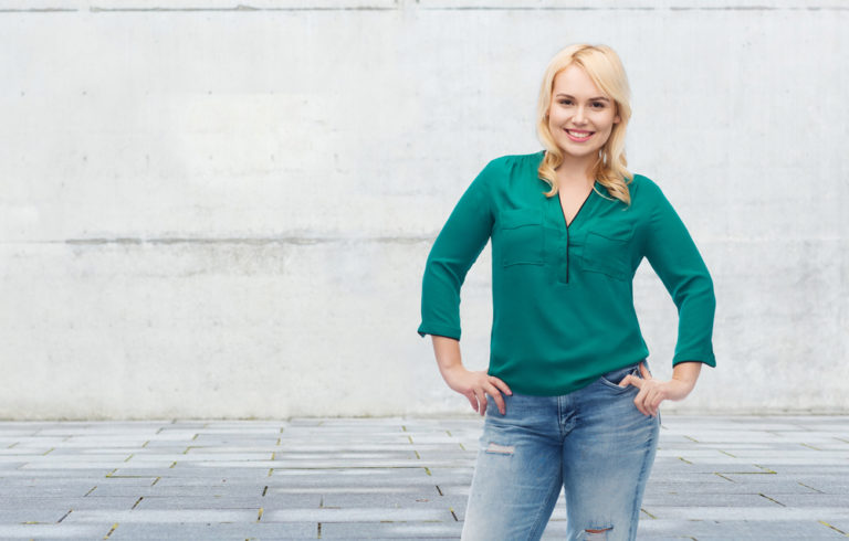 Woman with hands on hips smiling at camera
