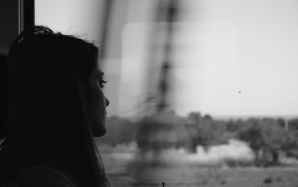 Black and white photo of woman looking out window