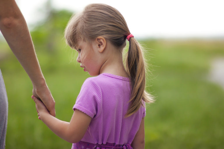 young girl with ponytail holding mother's hand